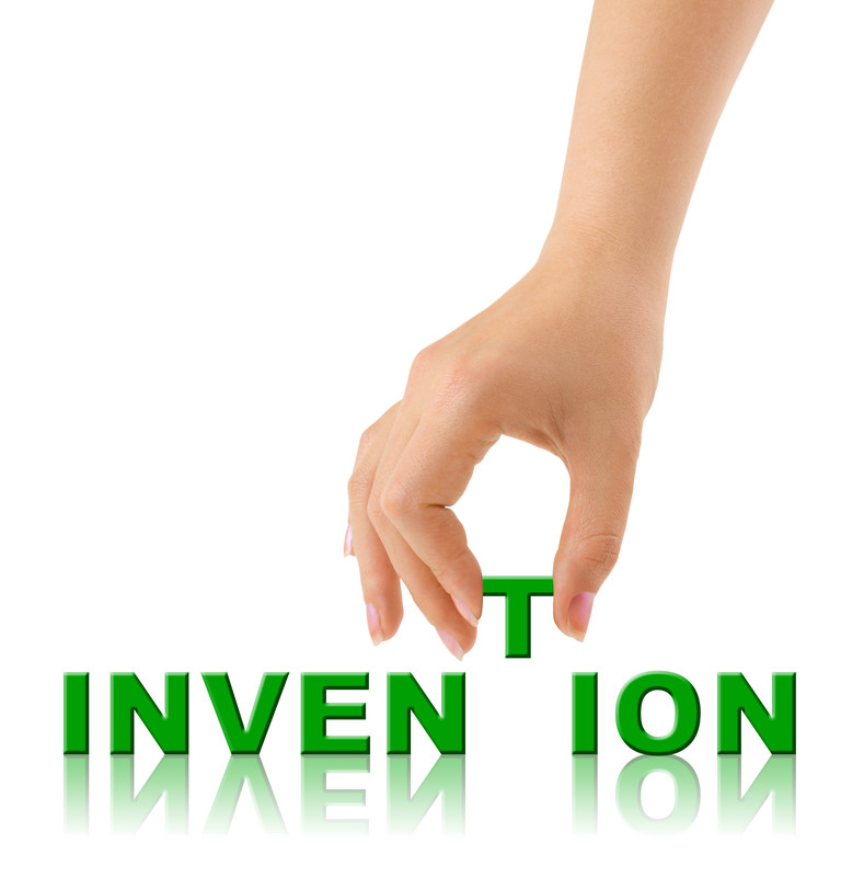 Invention word with the letter T being placed by a hand.